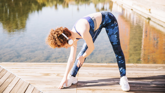 woman-in-headphone-exercising-on-pier_23-2147755497